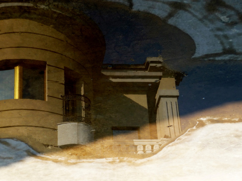 Spiegeling - Reflectie van een stuk van het hotel in een waterplas (en dan omgedraaid)
