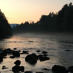 Nevel boven water tijdens zonsondergang