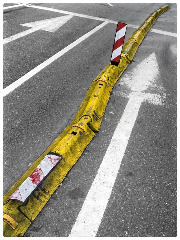 Street art - Zag later pas dat de foto een kleine beeldgrap bevat. De rechter rechter pijl lijkt tov de andere pijl vastgelopen in de verhoogde wegmar