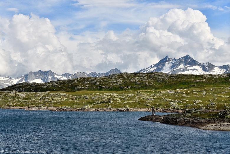GrimselPass - Wolkenhemel boven de besneeuwde bergpieken en het meer van de Totensee. Gelegen op de Grimselpass op 2165m hoogte in de Zwitserse Alpen