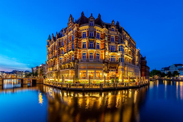 Hotel De L'Europe - De nacht treedt in bij Hotel De L'Europe in Amsterdam. Links nog een restje zonsondergang en rechts het blauwe uurtje. Omdat er no