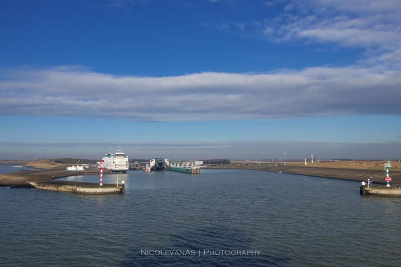 Texel aankomsthaven. - Het zonlicht valt mooi over de waddenzee.  De veerboot waar wij op zitten geeft een schaduw over de waddenzee.  Van dit uitzich