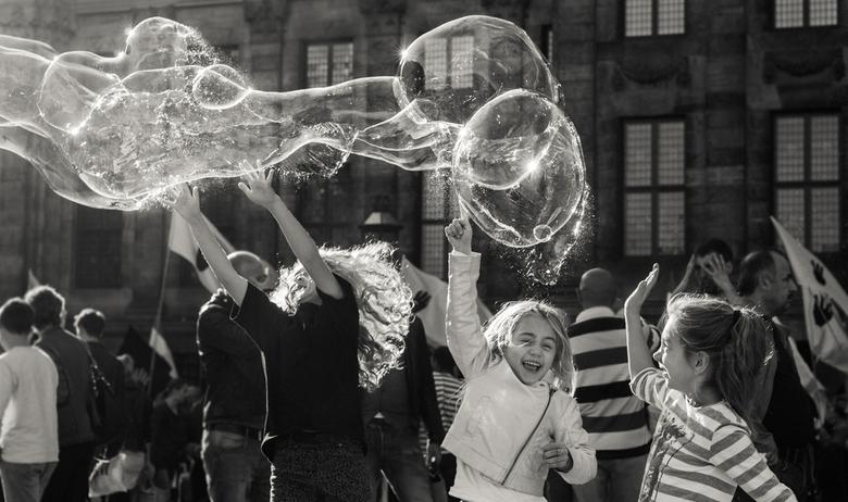 Playing with soap bubbles - Deze foto heb ik gemaakt midden op de Dam. In het midden van alle drukte (demonstratie) waren er kinderen met zeepbellen a