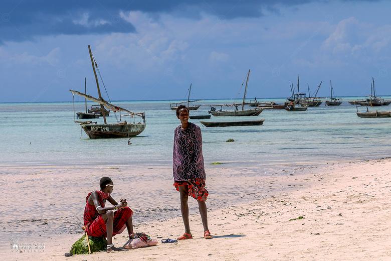 Zanzibar - Twee als masai-krijgers  verklede handelaren die brillen en sierraden aan de toeristen proberen te slijten op het strand van Nungwi in Zanz