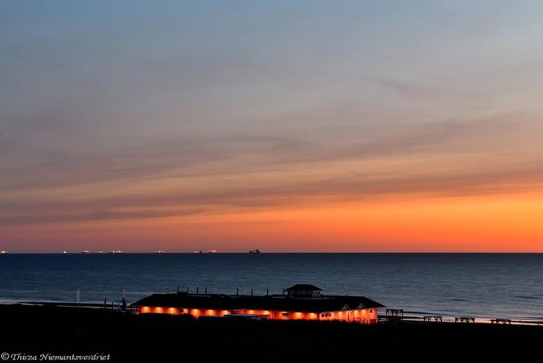 The Beach Club - Mooie zomeravond in mei, aan de kust bij Noordwijk. De lichtjes van een strandpaviljoen, passend bij het warme licht van de zonsonder