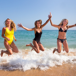 Drie meisjes springen op strand bij zee