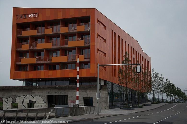 Hete Kolen. - Een vlammend oranjekleurige gevel boven op een koolzwart fundament van basalt. Het appartementencomplex Hete Kolen in Groningen ademt hi