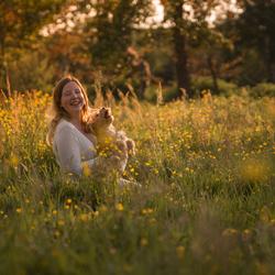 Gouden uur portret van spelend meisje met puppy tussen gele boterbloemen