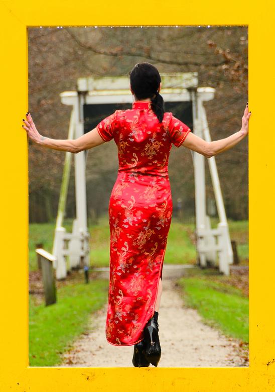 Oosterse in Ennemaborg 2 - Dame in rode oosterse jurk in het 'koude' Groningse landschap van Ennemaborg. Crop uit een andere foto uit dezelf