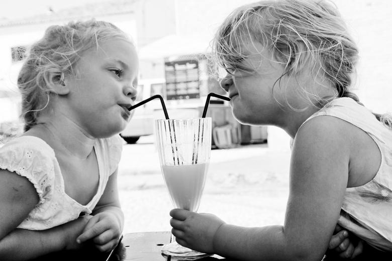 Samen delen - Twee meisje drinken samen uit een glas