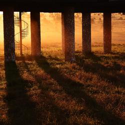 zonsopkomst doorheen paalwoningen