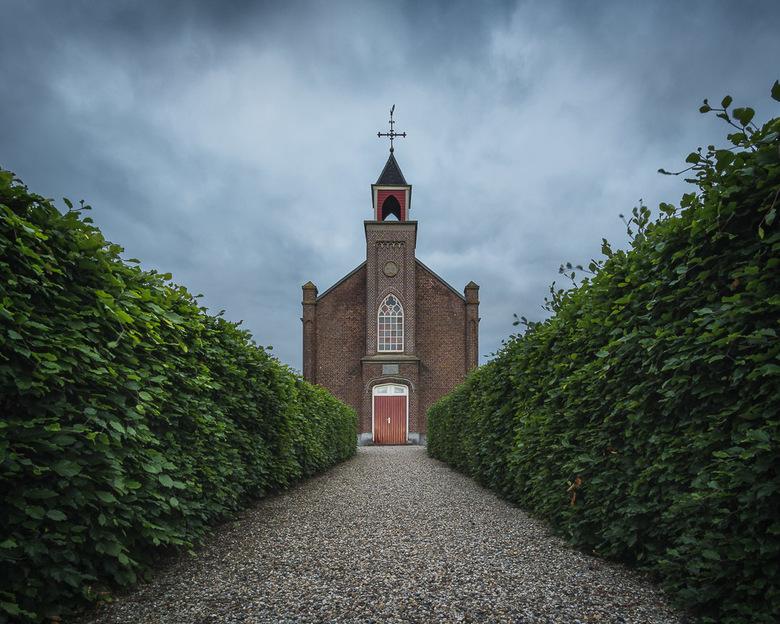 Red Door - Een kerk na zonsondergang onder een donkere wolken.