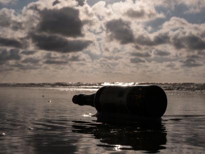 Fles op het strand - De lage camerastand lijkt de afmetingen van de fles te vergroten