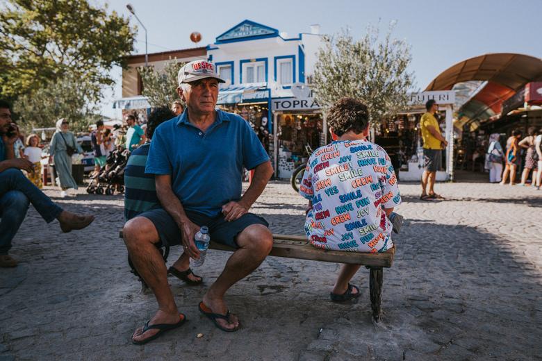 Grumpy vs Smile - Een norse Turkse meneer met een zure uitdrukking zittend op een bankje. Naast hem een jongen met een vrolijk t-shirt met de woorden