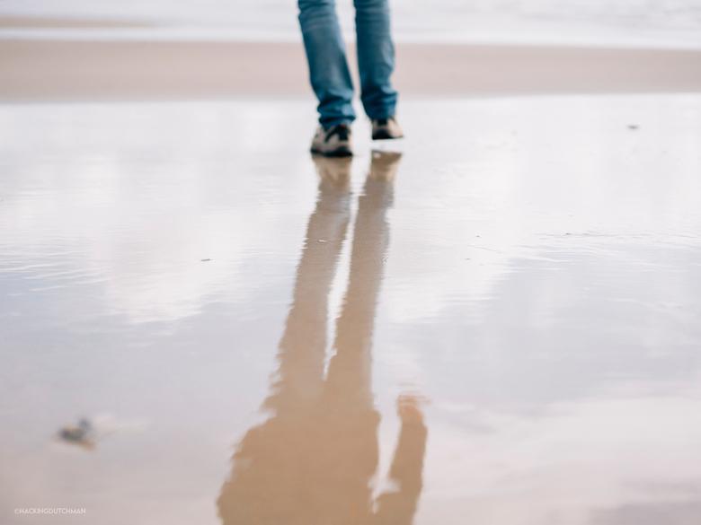 Reflectie - Reflectie van een persoon in het water op het strand.<br /> <br /> <br /> <br /> ©MotionMan 2020