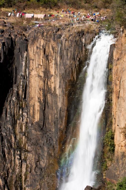 Doing Laundry - Afrikaanse mensen wassen hun kleding en laten dit ook ter plekke drogen naast een 95 meter hoge waterval, Howick Waterfalls, Kwa-Zulu