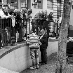 Straatbeeld Funchal Madeira. Twee mannen aan het kaarten en de rest kijkt toe.
