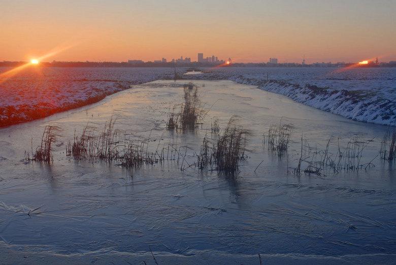 Winters Rotterdam weerkaatst - De zon komt op boven een winters Rotterdam en weerkaatst in een gebouw in het centrum en ten westen van de stad.