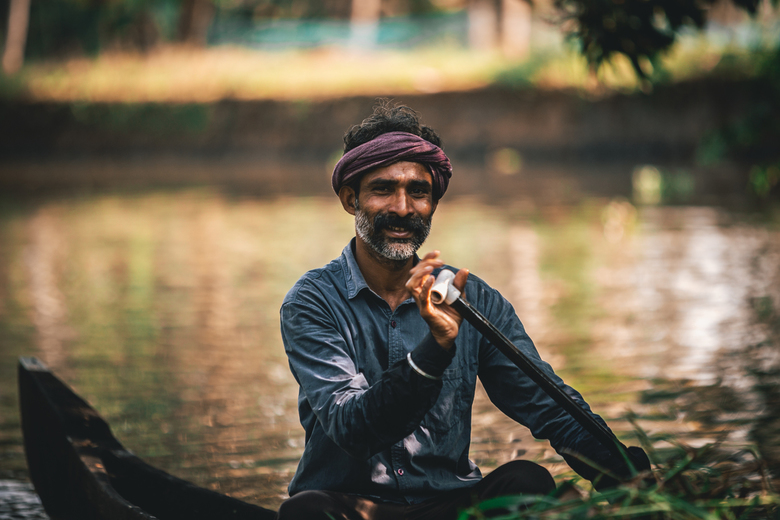 A day in Allepey - In the backwaters of Kerala (India) People still use boats as their main form of transportation, here is a man taking palm leaves f