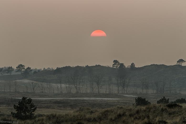 zonsondergang bij het vogelmeer - De zon verdwijnt achter achter de mistige wolken
