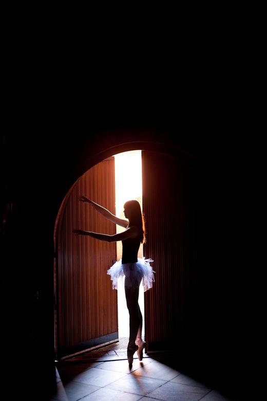 Ballerina - Ballerina gefotografeerd in het mooie ochtend licht door de deur van een kerk.