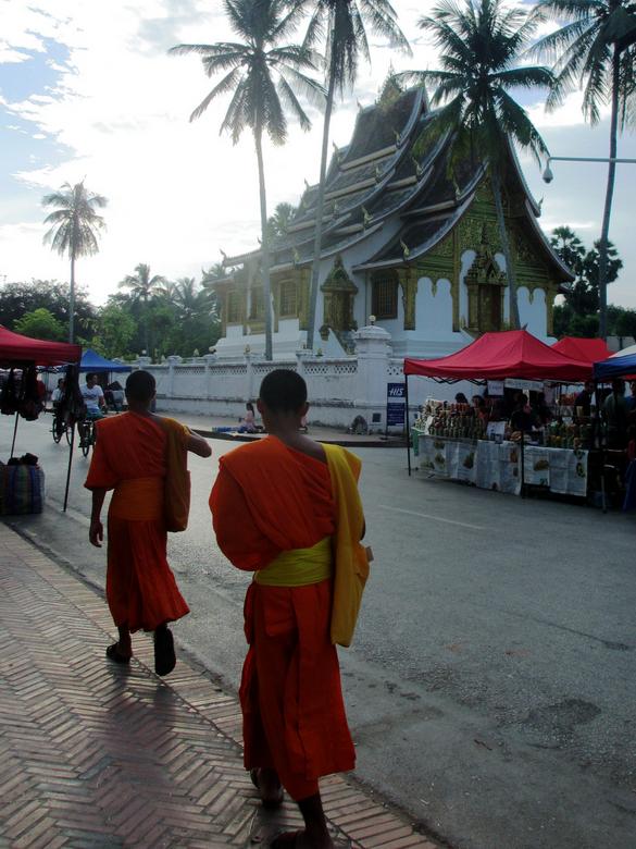 Laos, walking monks - In Luang Prabang liepen deze 2 jonge monniken voor mij door de straat. Het was rond half 6, de lokale bevolking begon net met he