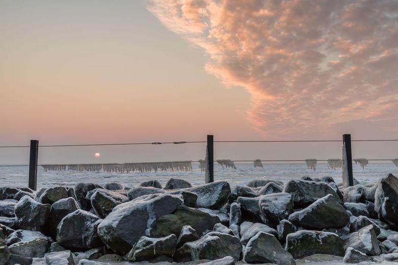 Ijskoude zonsopkomst bij het strandje van Oudeschild - Een ijskoude zonsopkomst met de ijsgang op de Waddenzee en de ijspegels aan de draden, maakten