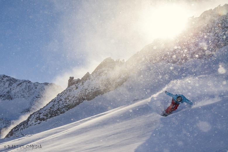 Sunny Spray - Door het opwaaien van de verse sneeuw ontstonden er allemaal glinsteringen in de lucht en lichtte de bergrand mooi op. Snowboarder maakt