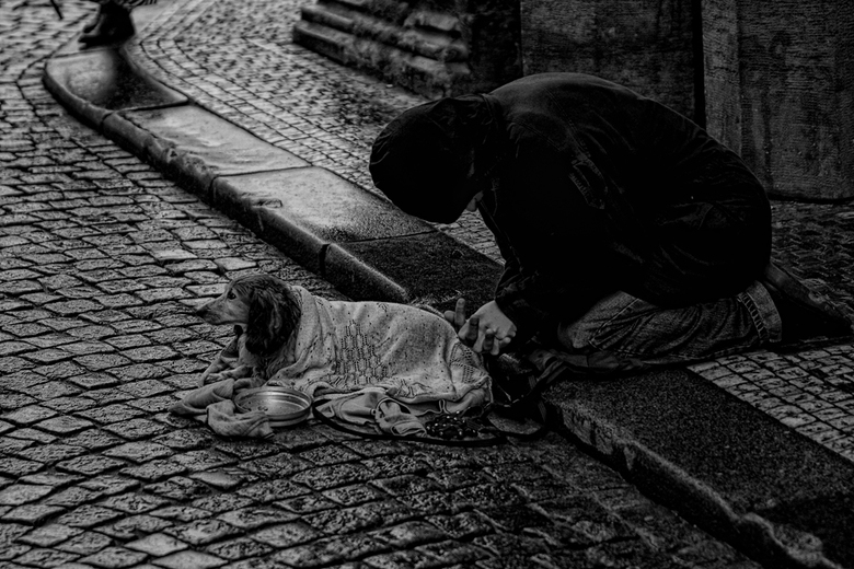 Streetlife x - Dakloze zwerver in een straat in Praag.Veel regen en erg koud,maar ondanks dat proberen hij en zijn hondje toch om wat geld te verdiene