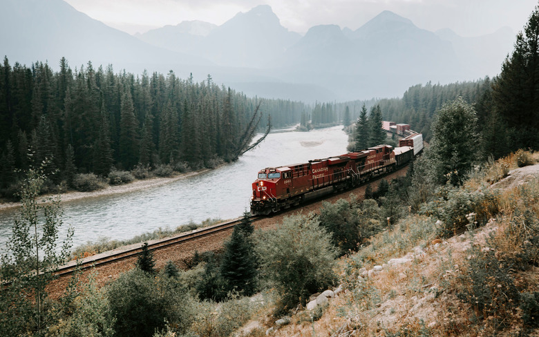 Travel by train - A Canadian Pacific manifest train sweeps around the famous Morant's Curve in the heart of the Banff National Park.
