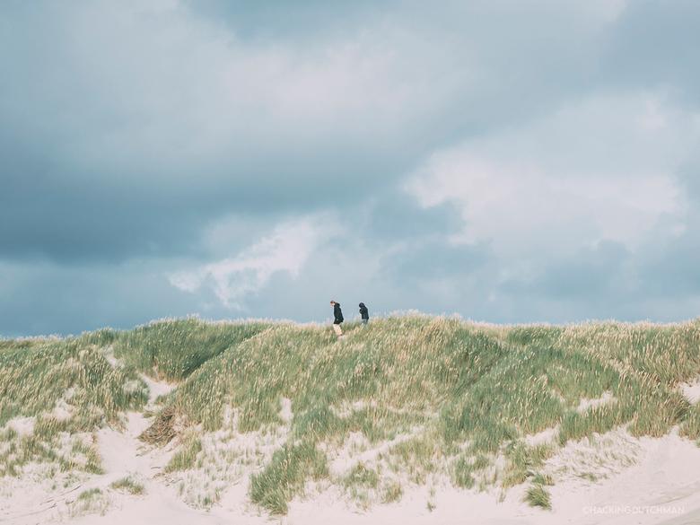 Bovenop - Twee mensen bovenop de strandduinen bij middelmatig weer met harde wind.<br /> <br /> <br /> <br /> ©MotionMan 2020