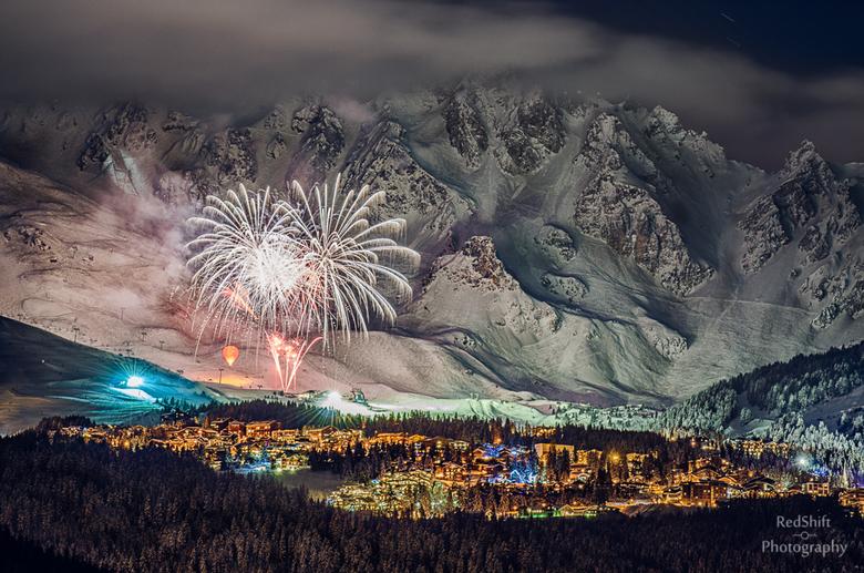 Fireworks on snow - Smal village Le Praz and Courchevel ski area, fireworks as seen from the distant mountain village.