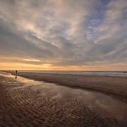 Zon met licht gekleurde wolken aan het strand