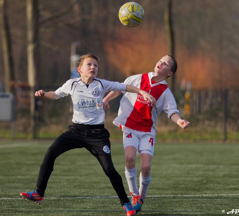 Equal soccer chances  - De bal hang precies tussen de jongens in; kwestie van wie heeft de snelste beweging om de bal richting zijn medespelers te kop