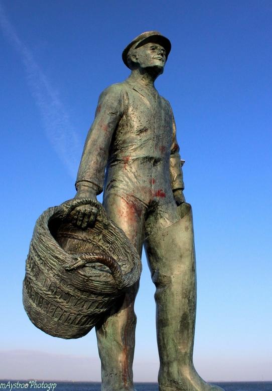 mosselman 2 - wakend bij de ingang van de vissershaven van yerseke het beeld van de mosselman