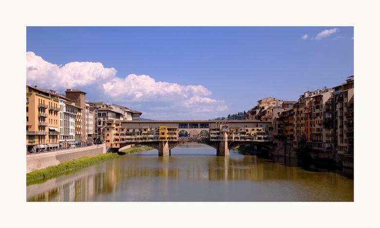 Florence - Zicht op de Ponte Vecchio over de rivier de Arno in Florence. Boven de heuvels ontstaan mooie stapelwolken.