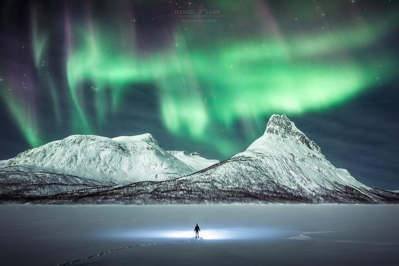 Dark Star - Een eenzame avonturier wandelt op een bevroren meer tussen besneeuwde bergen in het wilde Noordpoolgebied onder de Aurora Borealis. Noorwe