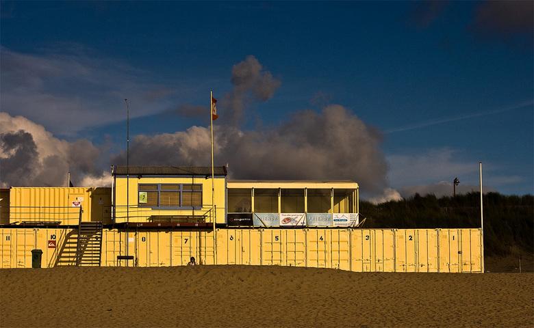 Katwijk aan Zee containers - Knalgeel gestapelde containers aan het strand van Katwijk in de namiddagzon.