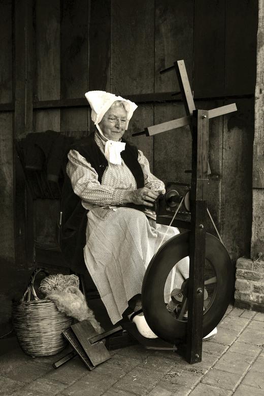 Like old times  - Een oude vrouw die achter een oud spinnewiel klossen touw rolt van vers geschoren wol.