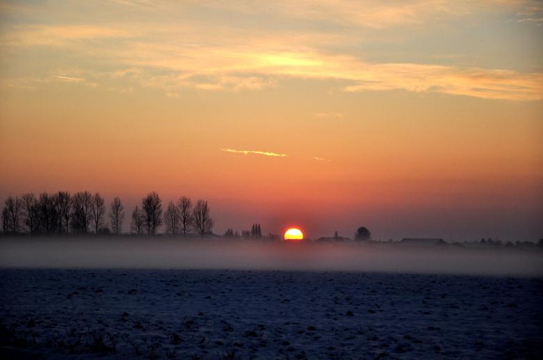zonsondergang - Mist over de besneeuwde akkers tijdens de zonsondergang.