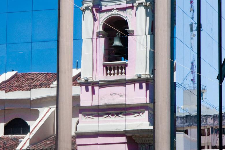 Weerspiegeling - De roze cathedraal weerspiegeld in het spiegelglas van het gebouw ernaast, plein in Salta.
