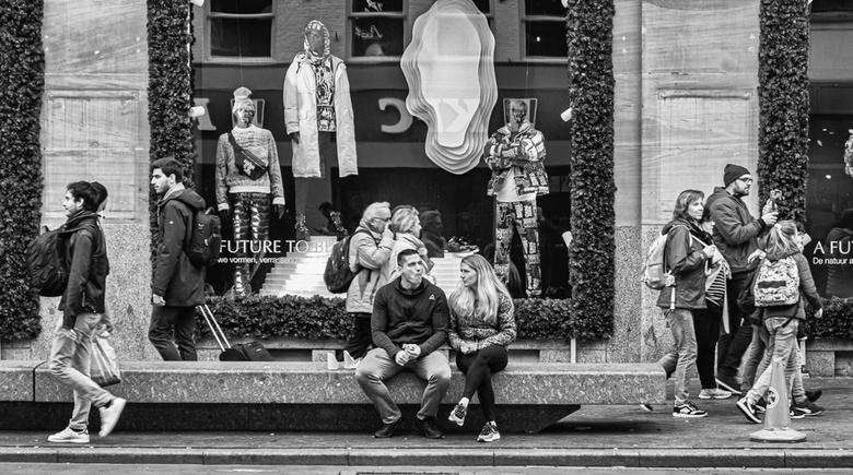 Een rust moment - Deze foto is gemaakt op het Damrak in Amsterdam. Twee mensen die even rustig zitten. Terwijl de andere mensen druk bezig zijn ,om va