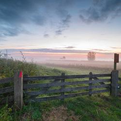 Polderlandschap in mist kort voor zonsopkomst