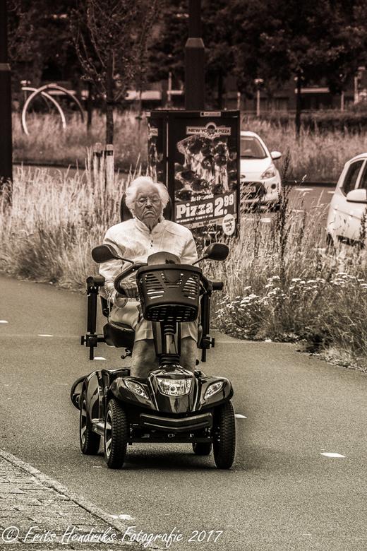 Je kan de komende bui al voelen aankomen - een oude vrouw in een scootmobiel probeert haar huis nog te halen net voor de wolkbreuk