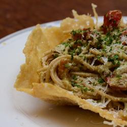 Pesto spaghetti in kommetje van parmezaanse kaas