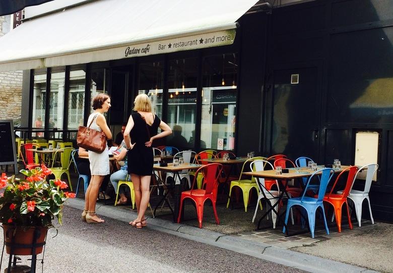 Onderonsje Besancon Frankrijk  - Twee Franse vriendinnen ontmoeten elkaar in Becanson op straat voor een kleurrijk terrasje. De dame met donker haar i