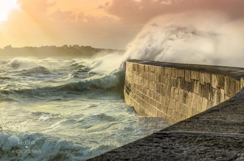 Big waves crushing on stone pier - Big waves crushing on curved stone pier, on stormy weather with vivid sunset, big tide, Saint Malo, France.