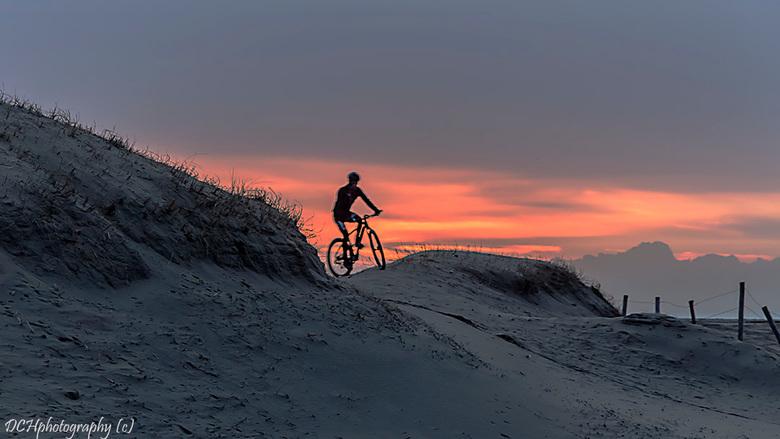 Dunebiken - Stond ik daar de zonsondergang te fotograferen en ineens kwam deze mountainbiker om de hoek kijken, klik deed ik toen en voilá.<br /> <br