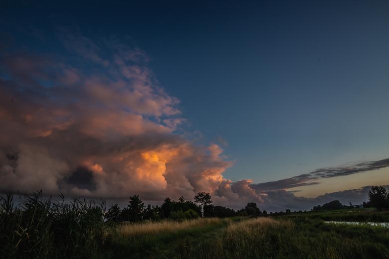 Zonsondergang als een schilderij - de wolken als het doek, de zon als schilder