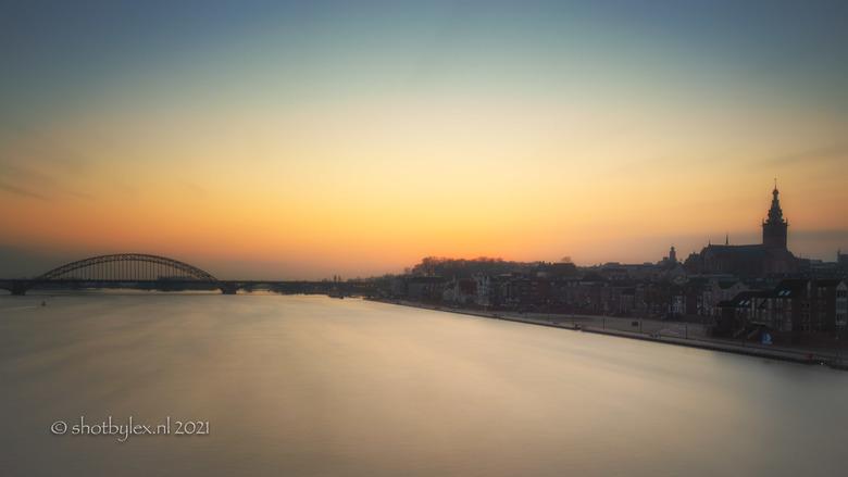 Nijmegen ontwaakt - Nijmegen ontwaakt met mooie ochtendkleuren boven het hoge water in de Waal.